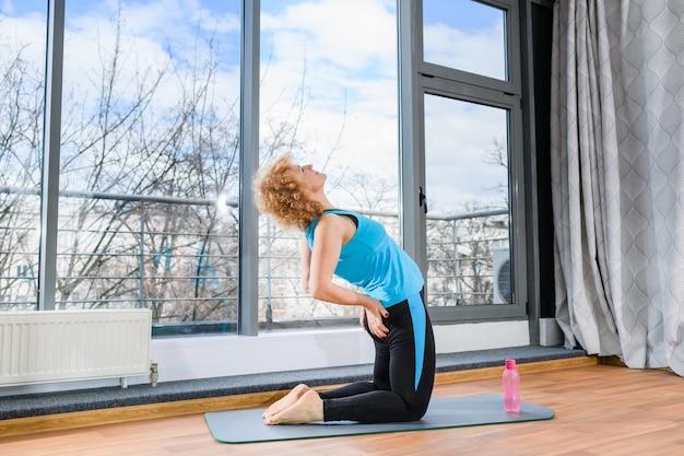 금발의 여자는 파란색 운동복에 스포츠 매트, 엉덩이에 손, 운동 피트니스 운동에 무릎에 머물