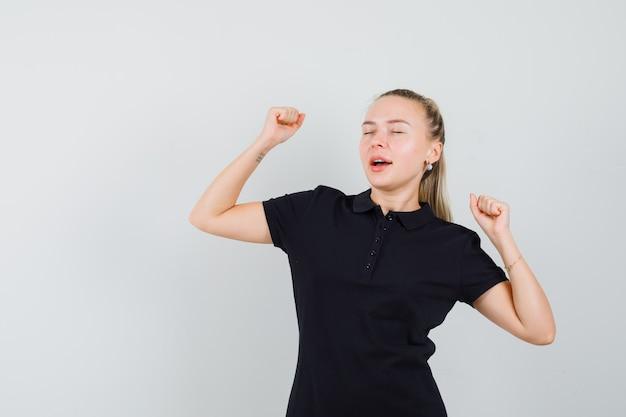 黒のtシャツでストレッチとあくびをし、疲れているように見えるブロンドの女性
