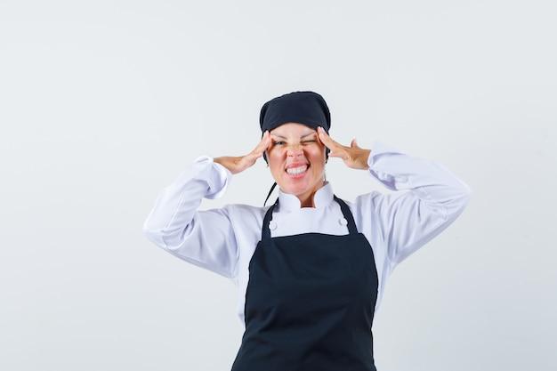 금발 여자 검은 요리사 유니폼에 손으로 눈을 스트레칭 하 고 예쁜 찾고.