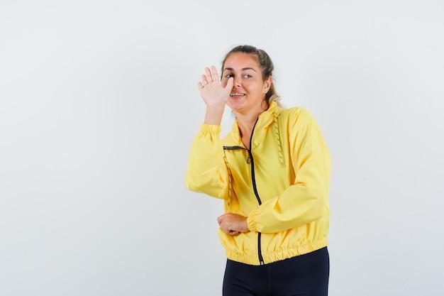Donna bionda che allunga la mano come saluto qualcuno in bomber giallo e pantaloni neri e sembra amabile