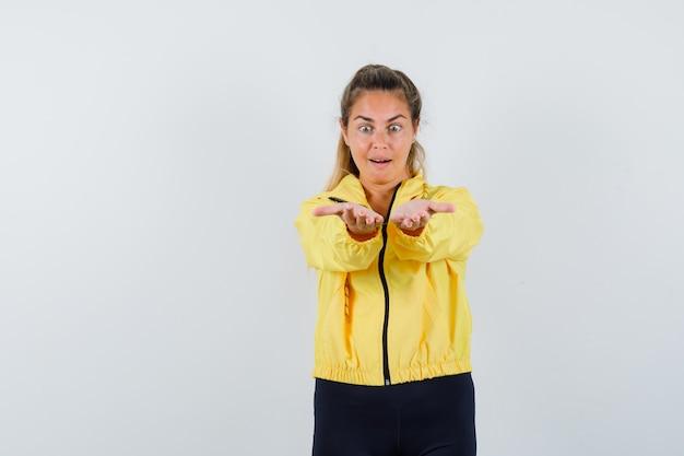노란색 폭격기 재킷과 검은 색 바지에 상상의 뭔가를 들고 놀란 찾고 금발의 여자 손을 스트레칭