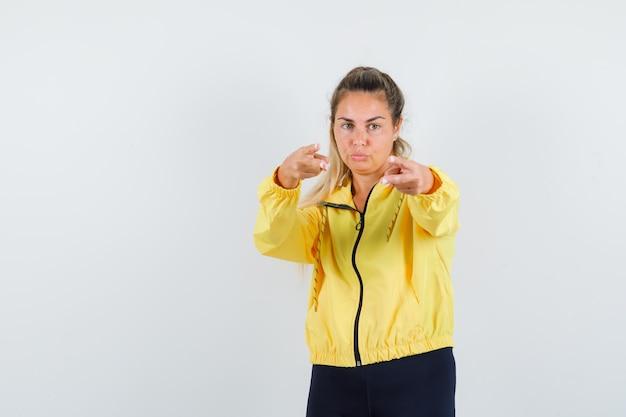 黄色のボンバージャケットと黒のズボンで来るように誘い、真剣に見えるように手を伸ばしているブロンドの女性