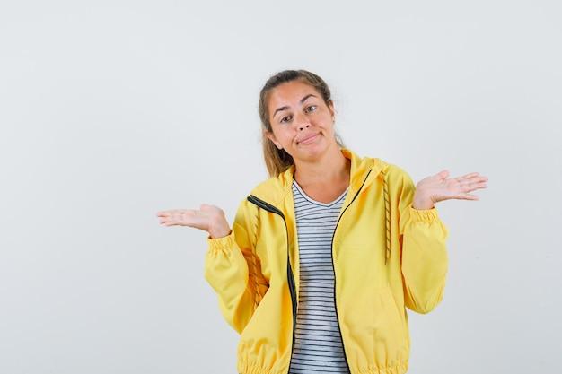 노란색 폭격기 재킷과 스트라이프 셔츠에 심문 방식으로 손을 뻗고 의아해 보이는 금발의 여자