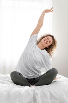 Blonde woman stretching on her bed in the morning