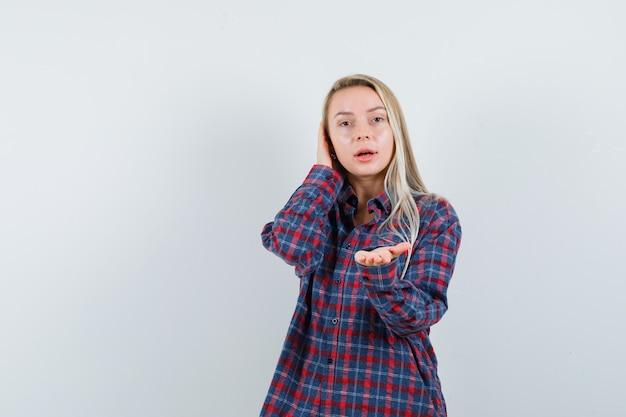 カメラに向かって片手を伸ばし、チェックのシャツを着て電話で話しているようなふりをして好奇心旺盛な金髪の女性。正面図。