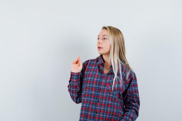 Блондинка протягивает одну руку во время разговора с кем-то в клетчатой рубашке и выглядит сосредоточенным, вид спереди.