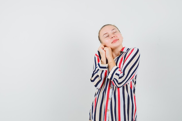 Donna bionda in camicetta a righe che appoggia la guancia sul palmo e sembra rilassata
