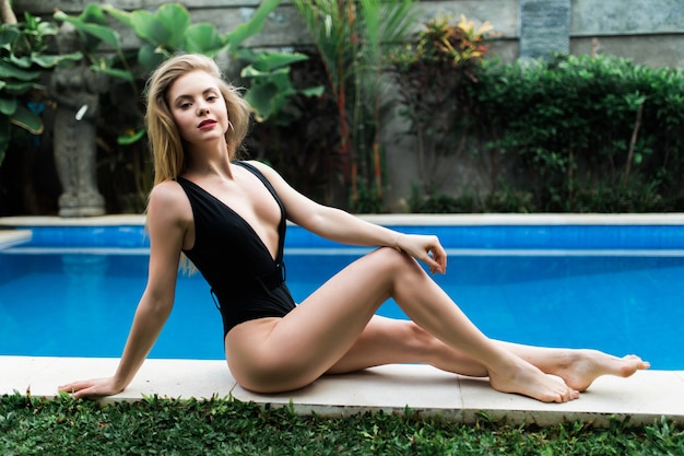 Блондинка загорает и лежит на краю бассейна у пейзажного бассейна на тропическом курорте
