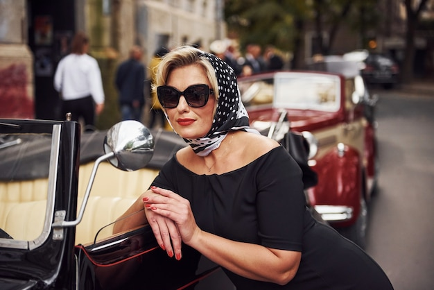 Blonde woman in sunglasses and in black dress leaning on old vintage classic car.
