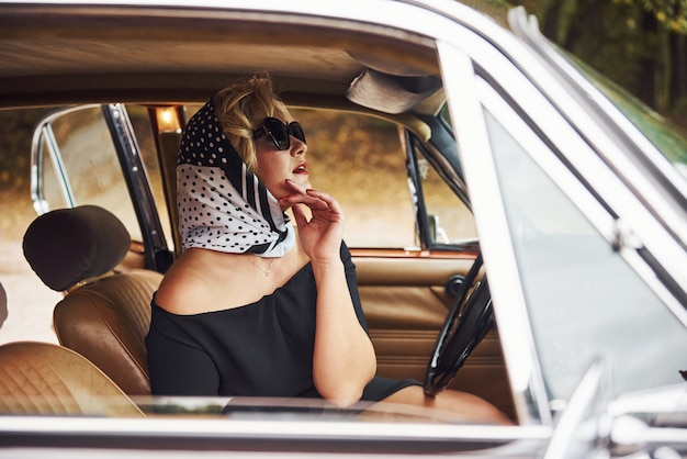 Blonde woman in sunglasses and in black dress sits in old vintage classic car.