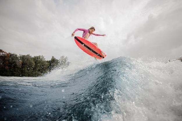 금발의 여자 서퍼 하늘을 파란색 튀는 파도 위로 점프