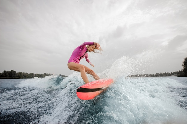 Blonde woman surfer riding down the blue splashing wave