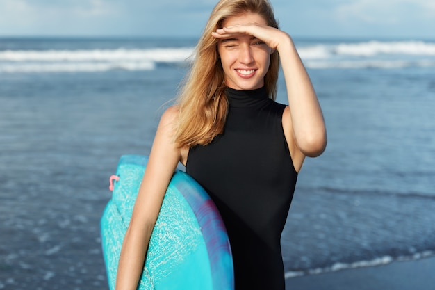 Blonde woman in swimsuit with surfboard on beach