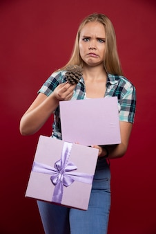 Blonde woman takes out an oak tree cone from the gift box and looks dissatisfied.