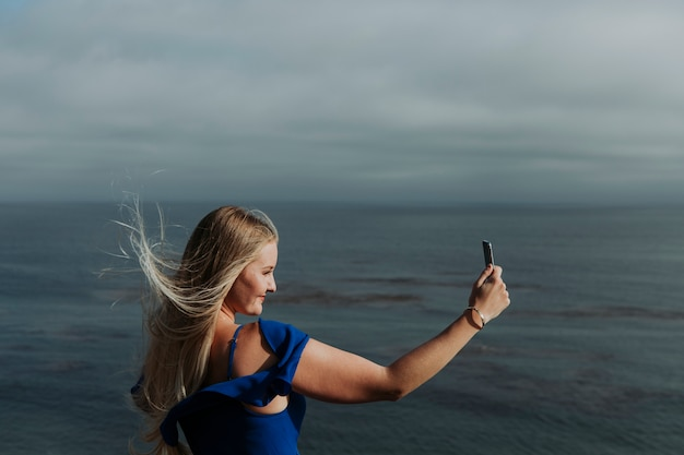 Blonde woman taking photos with her phone
