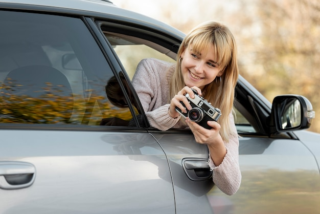 Blonde woman taking pictures from car