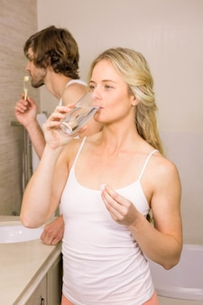 Blonde woman taking a pill with her boyfriend brushing his teeth in the bathroom at home