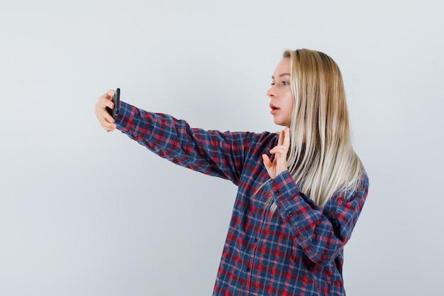 Donna bionda che cattura selfie e che mostra il segno di pace in camicia a quadri e sembra attraente, vista frontale.