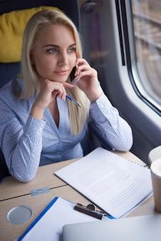기차에서 휴대 전화로 이야기하는 금발 여자