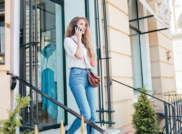 Блондинка женщина разговаривает по телефону на открытом воздухе