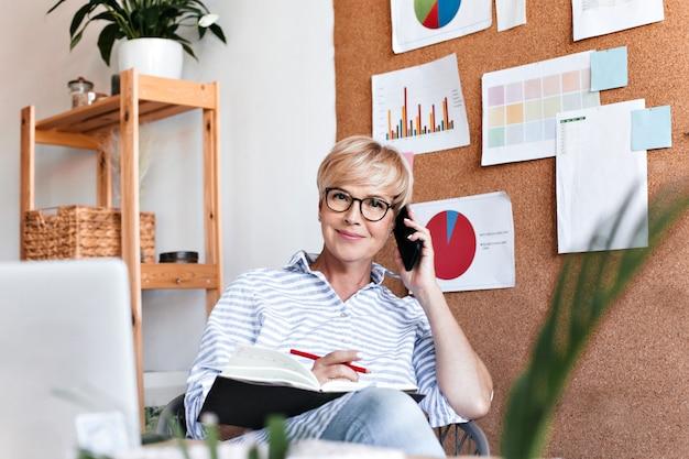 Блондинка женщина разговаривает по телефону и позирует с ноутбуком в офисе