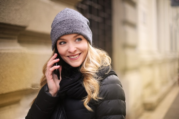 Blonde woman talking on the phone on the way