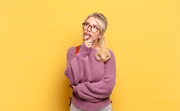 金髪の女性が考え、疑わしくて混乱し、さまざまな選択肢があり、どの決定を下すか疑問に思っています