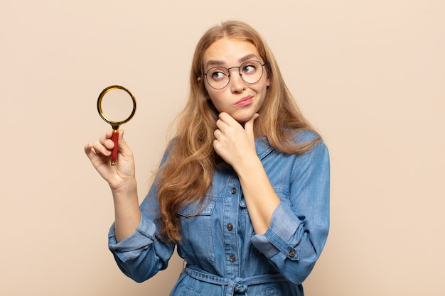 Блондинка думает, сомневается и сбивается с толку, с разными вариантами, задается вопросом, какое решение принять