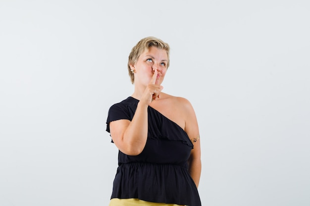 Blonde woman thinking something with finger on mouth in black blouse and looking pensive