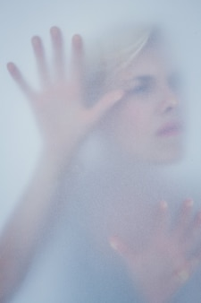 Blonde woman touching frosted glass