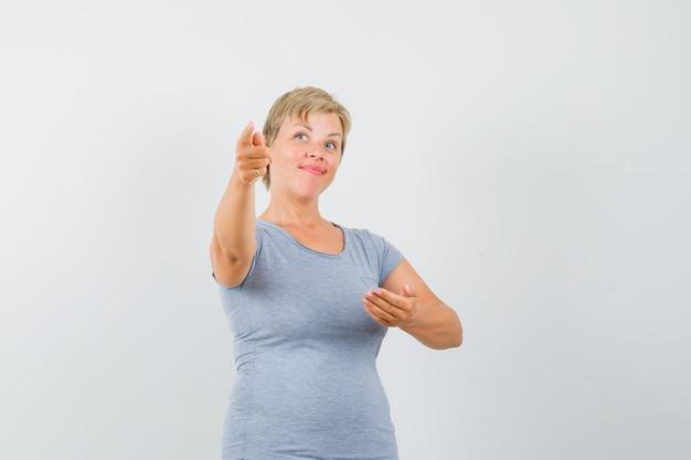 Donna bionda che prova a mostrare qualcosa in maglietta azzurra e che sembra ottimista, vista frontale.