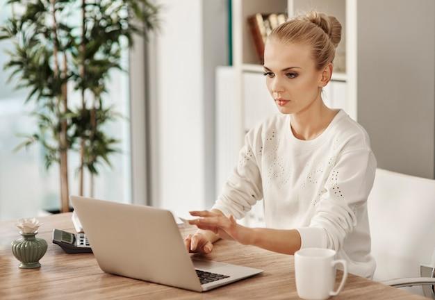 Blonde woman typing on laptop keyboard