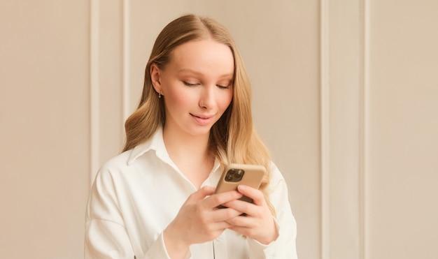 Блондинка использует приложение для знакомств на телефоне, проводя пальцем по экрану и касаясь его