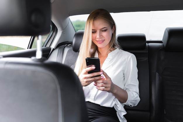 Blonde woman using a phone in the car