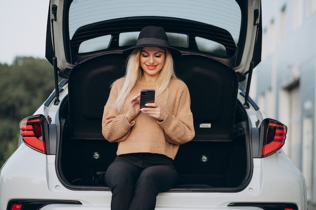Blonde woman using phone and sitting in car trunk