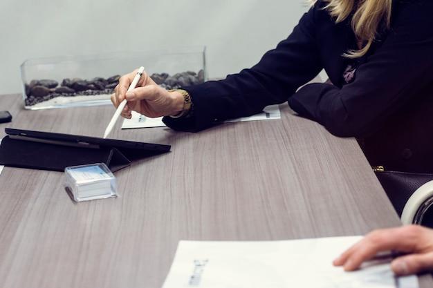 Блондинка женщина с помощью планшета на встрече в офисе с деловыми партнерами