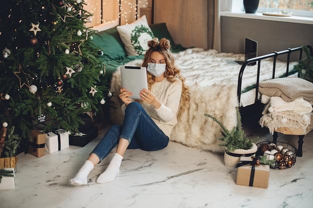 Videochiamata donna bionda tramite pad dalla camera da letto a natale. pandemia e concetto di blocco.