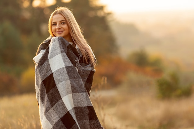 Blonde woman warming herself with a big scarf