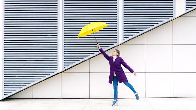 白い幾何学的な背景に黄色の傘でジャンプする紫色のコートを着ている金髪の女性。