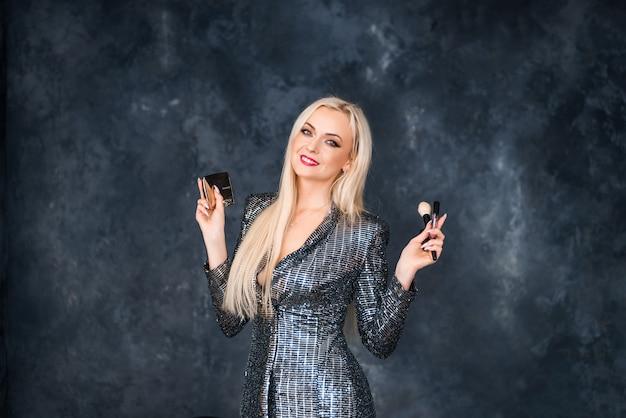 Блондинка в блестящем платье с инструментами для макияжа