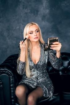 Блондинка в блестящем платье сидит на диване и смотрит в зеркало, делая макияж