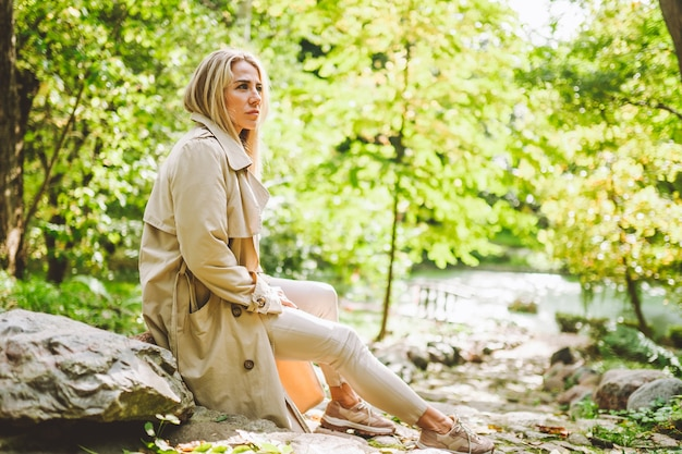 Blonde woman wearing a beige trench on a sunny day at the park.