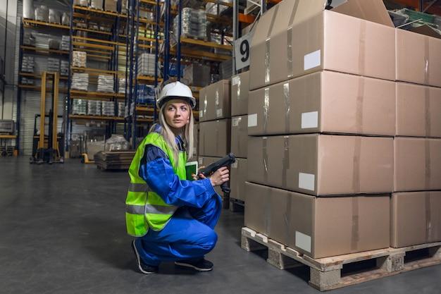Блондинка женщина в синей форме желтой куртке hardhat, держащей устройство, глядя на корточки на складе.