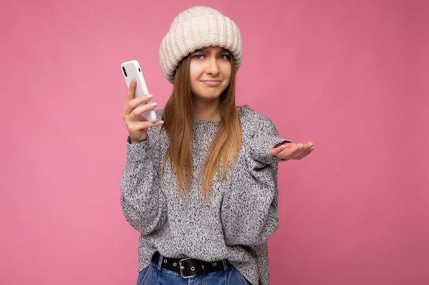 Blonde woman wearing casual grey sweater and beige hat isolated over pink wall holding in hand and using mobile phone  and having doubts.