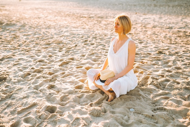긴 흰색 드레스를 입은 금발의 여자는 눈을 감고 빈 해변에 앉아 있습니다.