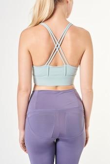 Donna bionda che indossa un reggiseno sportivo con cinturino incrociato