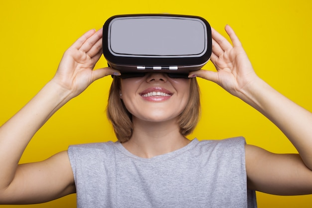Blonde woman wearing a virtual reality headset on a yellow studio wall smiling toothily