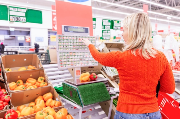 A blonde woman weighs fruits in a supermarket. back view.