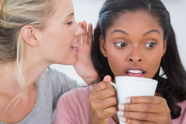 Blonde woman whispering secret to her friend