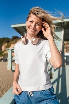 Donna bionda in maglietta bianca in spiaggia